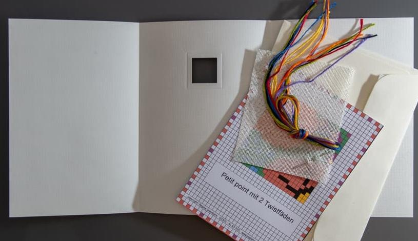 Tütenpackung mit Zählmuster, Leinen, DMC-Garn und Nadel und Passepartoutkarte